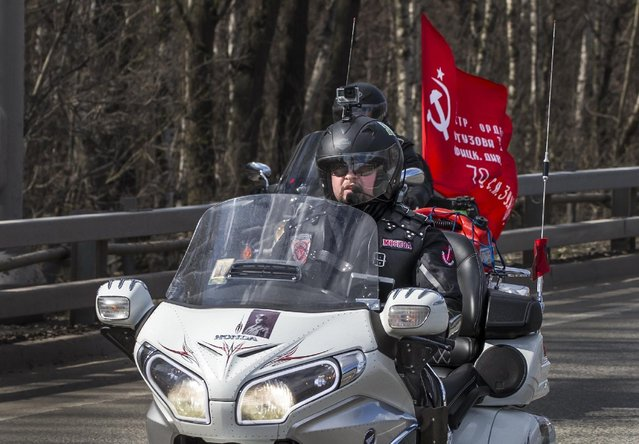 A group of Russian bikers carry a copy of the Victory banner, which was raised by Soviet soldiers on the Reichstag in Berlin, as they begin their trip  to Germany to mark the 70th anniversary of Soviet victory over Nazi Germany, in Moscow, Saturday, April 25, 2015. (Photo by Alexander Zemlianichenko/AP Photo)