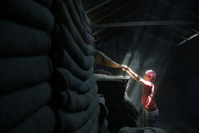 A worker stacks jute sacks in a shop in Munshiganj, Bangladesh, March 25, 2019. (Photo by Mohammad Ponir Hossain/Reuters)