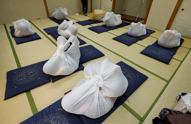 """Participants perform Otonamaki, which translates as """"adult wrapping"""", a new form of therapy where people are wrapped in large swaddling cloth to alleviate posture problems and stiffness, at a session in Asaka, Saitama prefecture, Japan, February 4, 2017. (Photo by Toru Hanai/Reuters)"""