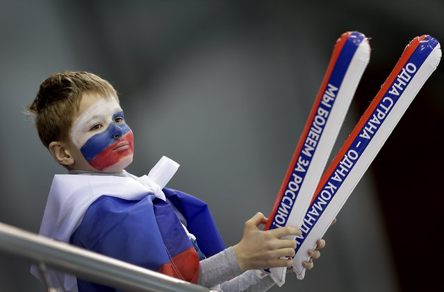 A Russian boy's is painted in the colors of the Russian national flag as he cheers the Russian women's curling team on with thunder sticks as they compete against Denmark at the 2014 Winter Olympics, Monday, February 10, 2014, in Sochi, Russia. (Photo by Wong Maye-E/AP Photo)