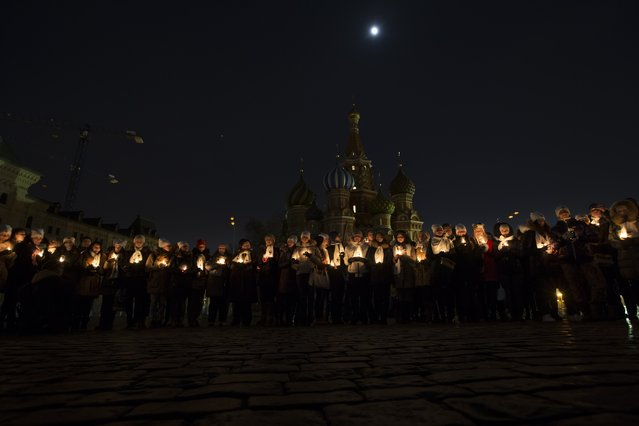 People holding candles mark Earth Hour after the lights are switched off  in front of St. Basil Cathedral on Red Square in Moscow, Russia, Saturday, March 19, 2016. The participants said they also used the event to pay tributes to the victims of the Dubai plane crash in southern Russia that killed all 62 people aboard on Saturday. (Photo by Alexander Zemlianichenko/AP Photo)