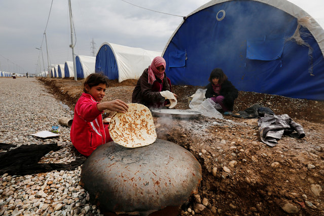 A displaced woman who fled the Islamic State stronghold of Mosul makes bread with their children at Khazer camp, Iraq, Feruary 9, 2017. (Photo by Muhammad Hamed/Reuters)