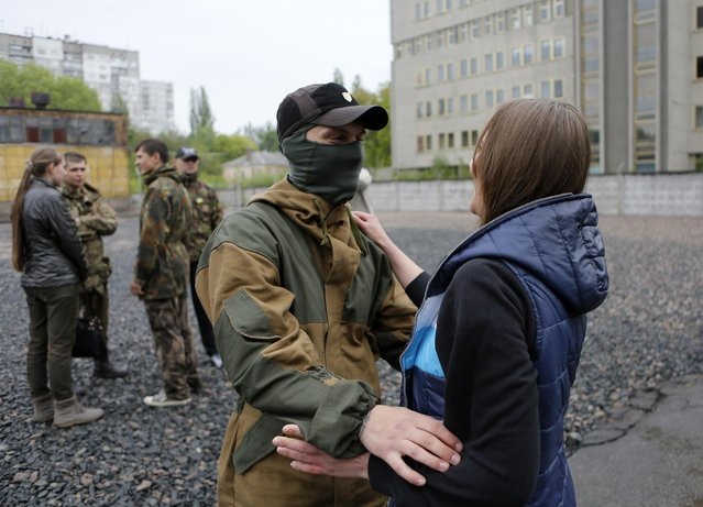 """Friends and relatives say goodbye to volunteers being sent to the eastern part of Ukraine to join the ranks of special battalion """"Azov"""" fighting against pro-Russian separatists, in Kiev, Ukraine, Thursday, May 7, 2015. (Photo by Sergei Chuzavkov/AP Photo)"""