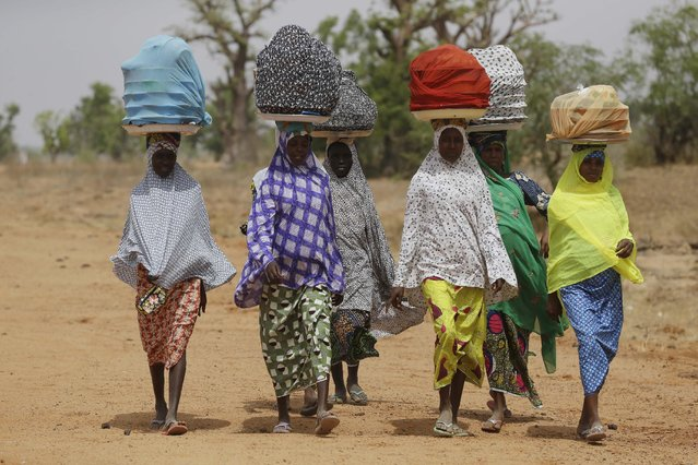 Fulani Women balance their wares on their head as they walk on the dirt road past a camp were women and children rescued by Nigerian soldiers from Boko Haram extremists at Sambisa Forest have taken refuge in Yola, Nigeria Monday, May 4, 2015. (Photo by Sunday Alamba/AP Photo)
