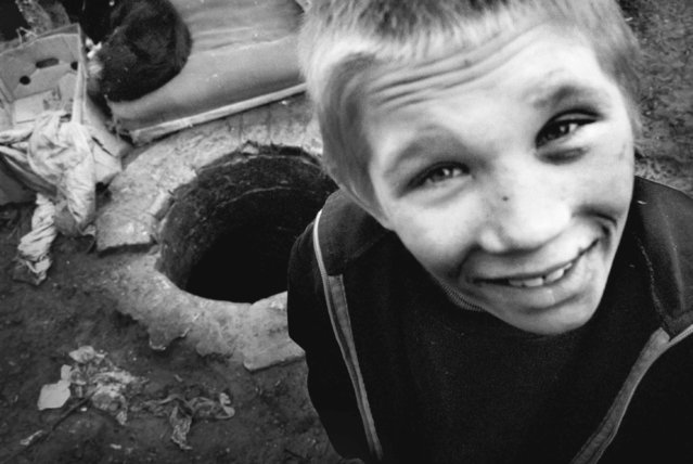 Artyom Selivanov, 9, has been living in this sewer in Kiev for over three years and has never attended school, 2002. His emotionally and physically scared brother refuses to contemplate returning home to their abusive alcoholic father. They feel that life on the streets is far better than the life they experienced at home. (Photo by Kurt Vinion /Getty Images)