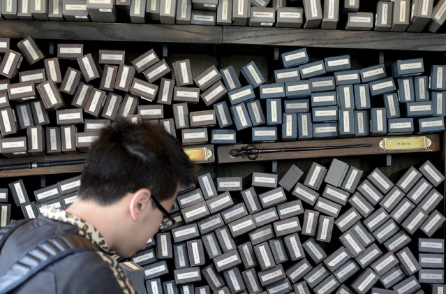 """A guest looks to purchase a magic wand inside Ollivanders during a soft opening and media tour of """"The Wizarding World of Harry Potter"""" theme park at the Universal Studios Hollywood in Los Angeles, California in this picture taken March 22, 2016. (Photo by Kevork Djansezian/Reuters)"""