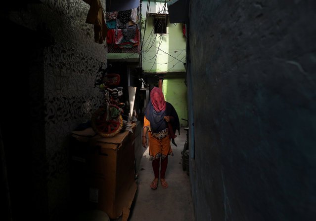 A woman walks through an alley in a residential area in New Delhi, India, April 30, 2019. (Photo by Anushree Fadnavis/Reuters)