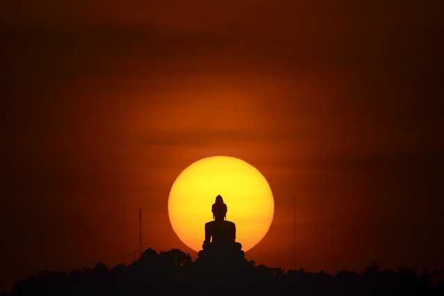 A sun sets behind a buddha statue in Phuket, Thailand March 18, 2016. (Photo by Athit Perawongmetha/Reuters)