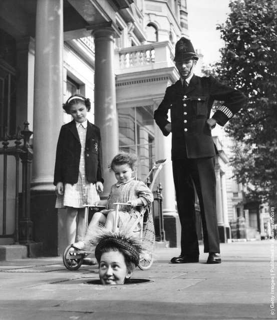 Former child actress Janette Scott emerges from a coal hole wearing one of Kensington-based designer Geynne Mallard's hats, to the interest of a policeman and two girls