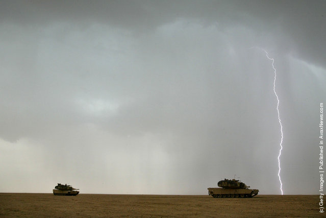 A lighting bolt flashes in the sky as U.S. Army M1A1 Abram tanks roll through the desert