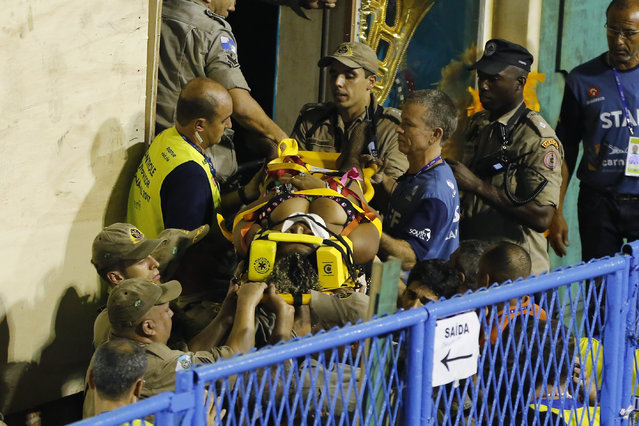 Firefighters carry an injured person on a stretcher to an ambulance during the performing of the Unidos da Tijuca samba school for the Carnival celebrations at the Sambadrome in Rio de Janeiro, Brazil, Tuesday, February 28, 2017. (Photo by Leo Correa/AP Photo)