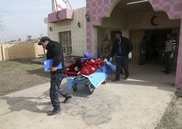 A Federal policeman, injured during fighting between Iraqi security forces and Islamic State militants is taken to a hospital after receiving first aid in a field clinic on the western side of Mosul, Iraq, Monday, February 27, 2017. (Photo by Khalid Mohammed/AP Photo)