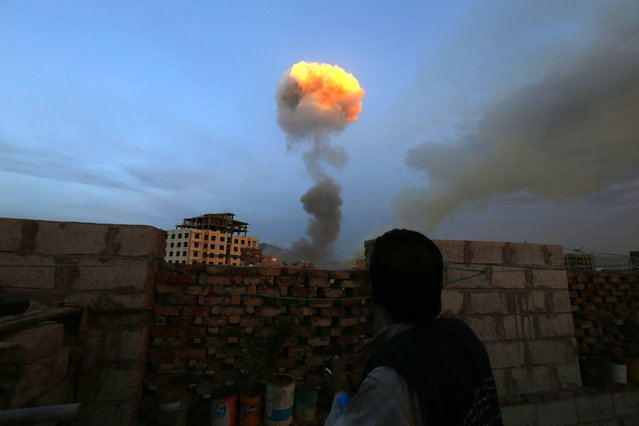 A Yemeni man looks at smokes raising above Sana'a after huge explosions rocked military weapon depots controlled by the Houthis as airstrikes carried out by the Saudi-led coalition hit the depot in Sana'a, Yemen, 11 May 2015. (Photo by Yahya Arhab/EPA)