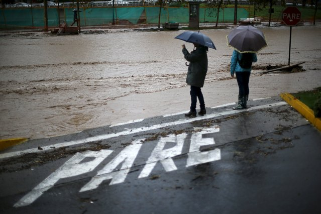 "People stand next to a flooded street in Santiago, April 17, 2016. The sign on the ground reads ""Stop"". (Photo by Ivan Alvarado/Reuters)"