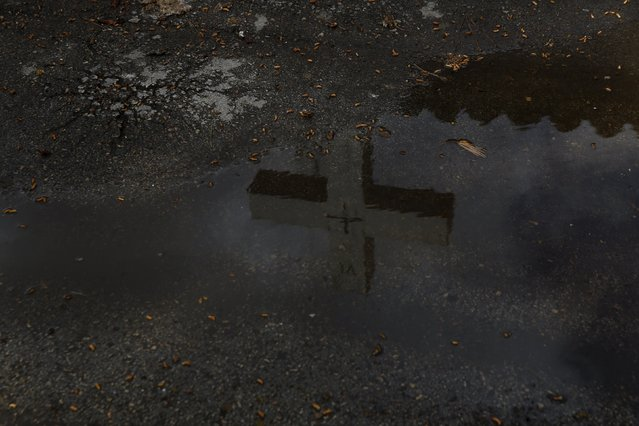 A cross is seen reflected in a puddle of water in Alcazar de San Juan, Spain, April 5, 2016. (Photo by Susana Vera/Reuters)