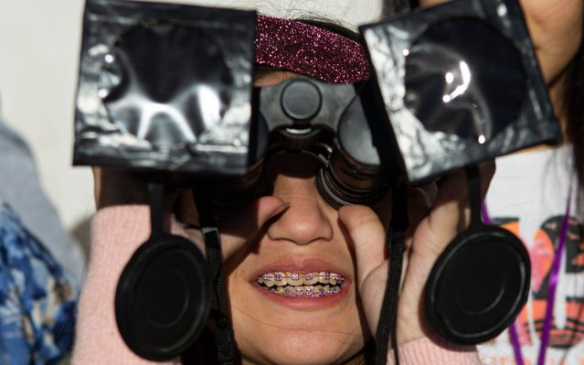 A girl tests special binoculars to view tomorrow's total solar eclipse near Central Park in La Higuera, Chile, Monday, July 1, 2019. Tourists and scientists will gather in northern Chile, one of the best places in the world to watch the next the eclipse that will plunge parts of South America into darkness. (Photo by Esteban Felix/AP Photo)