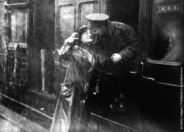 A soldier saying goodbye to a loved one in the rain at Victoria station, London, as he leaves for the front