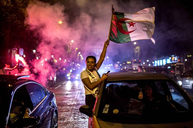 Algeria supporters celebrate on the Champs-Elysees in Paris, near the Arc de Triomphe, after Algeria won the Africa Cup of Nations final soccer match against Senegal, Friday, July 19, 2019. (Photo by Rafael Yaghobzadeh/AP Photo)
