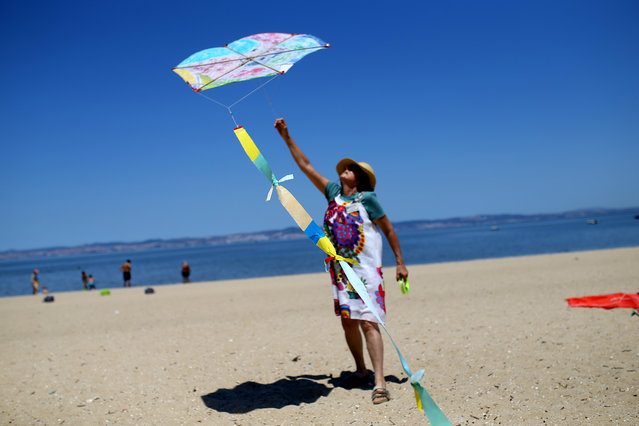 A woman flies her kite during an international kite festival in Alcochete, near Lisbon, Portugal, Sunday, June 28, 2015. (Photo by Francisco Seco/AP Photo)