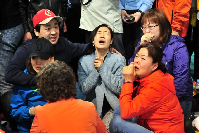 South Korean relatives of passengers on board a capsized ferry cry as they wait for news about their loved ones, at a gym in Jindo on April 17, 2014. The frantic search for nearly 300 people, most of them schoolchildren, missing after a South Korean ferry capsized extended into a second day on April 17, as distraught relatives maintained an agonising vigil on shore. (Photo by Jung Yeon-Je/AFP Photo)