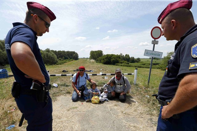 Police guard migrants from Syria who have crossed the border from Serbia to Hungary, walking on the dam near the Tisza river near the city of Szeged, Hungary, on June 29, 2015. So far this year more than 60,000 migrants have crossed into Hungary illegally, most of them coming from Kosovo, Syria and Afghanistan. (Photo by Laszlo Balogh/Reuters)