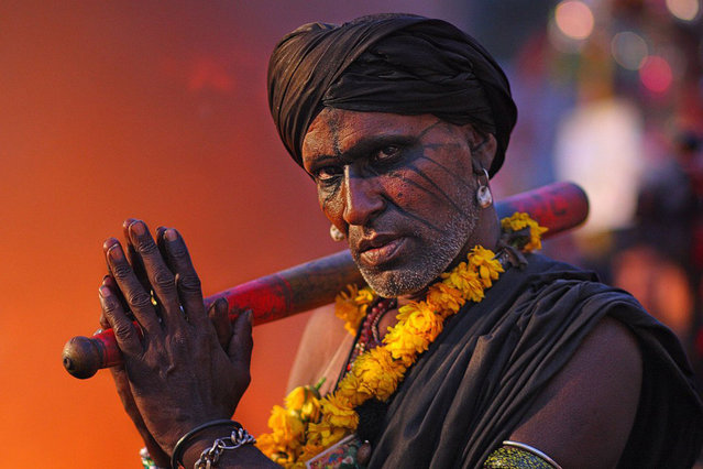 A devotee at Mela Chiraghan, an annual Festival of Lights in Pakistan. He was standing in front of a huge fire, casting the orange glow in the background. Lahore, Pakistan. (Photo by Yasir Nisar/Smithsonian.com)