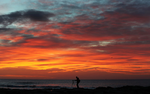 A photographer captures the sunrise over Tyne and Wear, Whitley Bay, England on March 13, 2017. (Photo by Owen Humphreys/PA Wire)