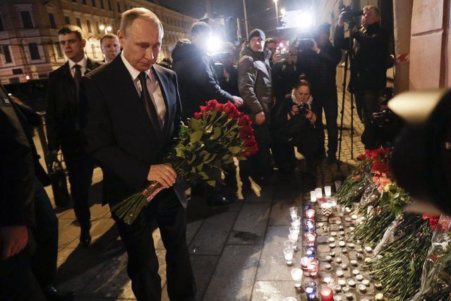 Russian President Vladimir Putin, left, lays flowers at a place near the Tekhnologichesky Institut subway station in St.Petersburg, Russia, Monday, April 3, 2017. (Photo by Dmitri Lovetsky/AP Photo)