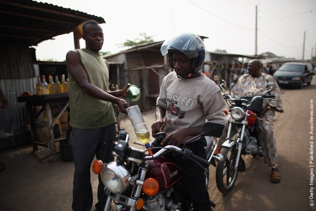 A vendor sells fuel, known locally as 'Kpayo', at the side of the road in Cotonou, Benin