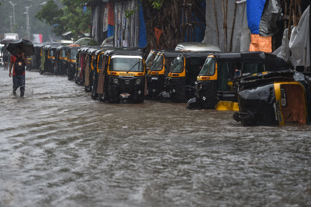 A pedestrian wades through a waterlogged street next to a line of auto rickshaws in heavy rain in Mumbai on September 4, 2019. (Photo by Punit Paranjpe/AFP Photo)