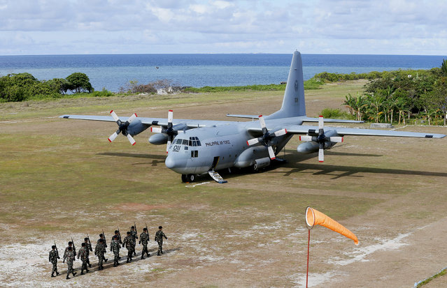 Philippine troops march as a Philippine Air Force C-130 transport plane carrying Philippine Defense Secretary Delfin Lorenzana, Armed Forces Chief Gen. Eduardo Ano and other officials, sits on the tarmac at the Philippine-claimed Thitu Island off the disputed Spratlys chain of islands in the South China Sea Friday, April 21, 2017 in western Philippines. Their visit Friday was aimed to assert the country's claim to the heartland of a disputed area where China is believed to have added missiles on man-made islands. The South China Sea issue is expected to be discussed in the 20th ASEAN Summit of Leaders next week. Seen in the background above the horizon, center, is the Chinese man-made island of Subi Reef. (Photo by Bullit Marquez/AP Photo)