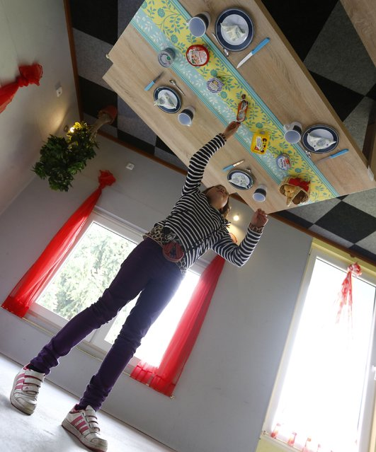 """Dutch tourist  Nova inspects the dining table inside the """"Crazy House"""", which is completely built upside-down, in the village of Affoldern near the Edersee lake, May 7, 2014. Three friends came up with the idea to build the tourist attraction, which cost about 200,000 euros and took some six weeks to complete. (Photo by Kai Pfaffenbach/Reuters)"""