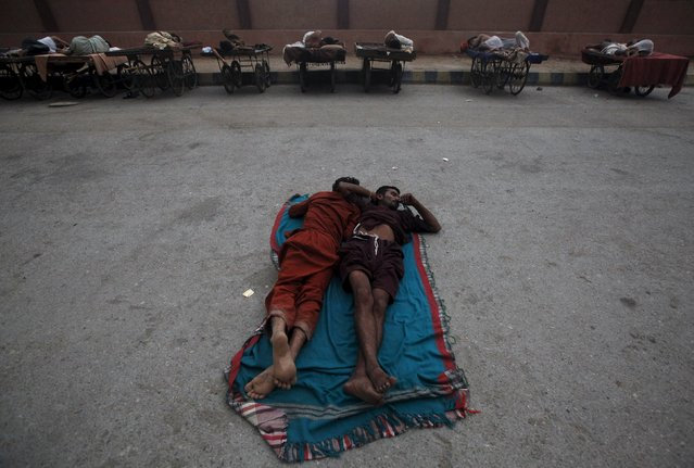 Men sleep on a street in the early morning to escape the heat during a major power breakdown in Karachi, Pakistan, July 8, 2015. A K-Electric spokesman said that almost half of Karachi city fell into darkness after the main power line from Bin Qasim power plant tripped on Tuesday evening, local media reported. (Photo by Athar Hussain/Reuters)
