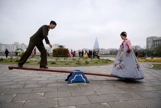 A bride and groom pose on a seesaw during a wedding photo shoot at a park in Pyongyang on April 18, 2019. (Photo by Ed Jones/AFP Photo)