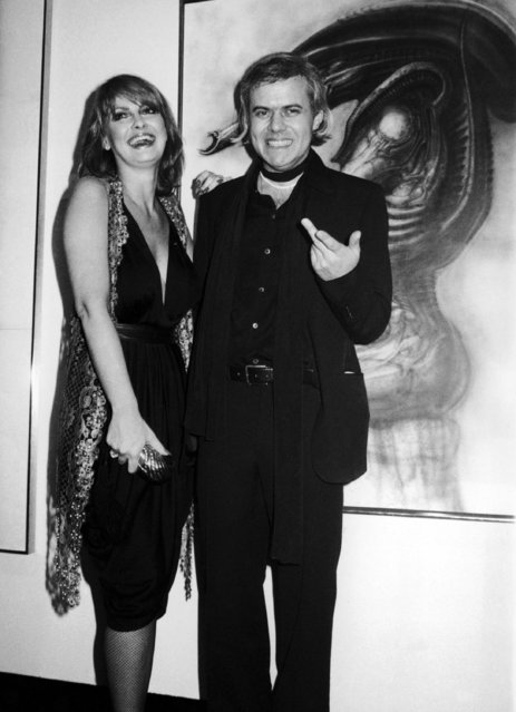 "Swiss Artist H.R. (Hansruedi) Giger, who has been nominated for an academy award for his visual effects for the movie ""Alien"", poses with Anneka Di Lorenzo in front of one of his paintings at the opening of an exhibition in New York on Monday, April 8, 1980. (Photo by AP Photo/Bocklett)"