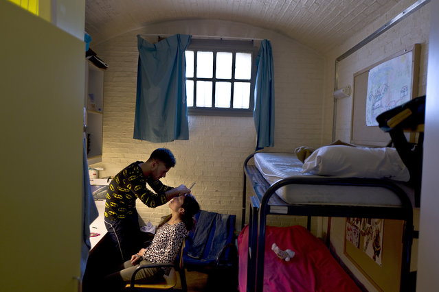 In this Sunday, May 1, 2016 photo, Yazidi refugee Yassir Hajji, 24, from Sinjar, Iraq, adjusts the eyebrow of his wife Gerbia,18, at their room in the former prison of De Koepel in Haarlem, Netherlands. (Photo by Muhammed Muheisen/AP Photo)