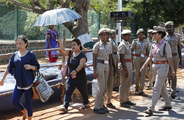 A group of tourists walk past police personnel keeping guard at Mamallapuram, where Indian Prime Minister Narendra Modi and Chinese President Xi Jinping will hold their first meeting and dinner in southern India, Friday, October 11, 2019. Xi Jinping is coming to India to meet with Prime Minister Narendra Modi on Friday, just weeks after Beijing supported India's rival Pakistan in raising the issue of New Delhi's recent actions in disputed Kashmir at the U.N. General Assembly meeting. (Photo by Manish Swarup/AP Photo)
