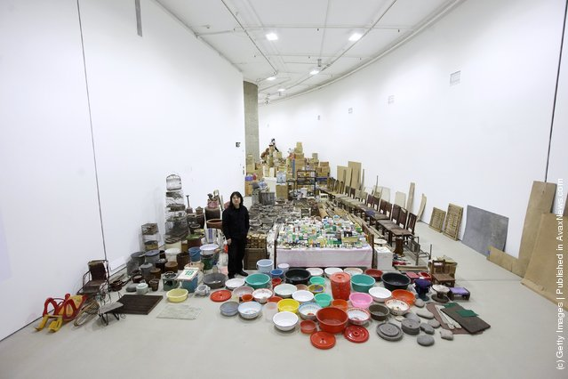 """Chinese artist Song Dong stands in his installation entitled """"Waste Not"""" in The Curve at the Barbican Art Gallery"""
