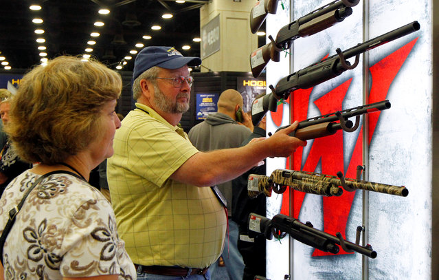 Gun enthusiasts look over Winchester guns at the National Rifle Association's annual meetings & exhibits show in Louisville, Kentucky, May 21, 2016. (Photo by John Sommers II/Reuters)