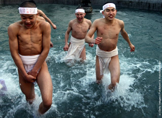 Japanese men wear loincloths as they splash about in freezing cold water during Saidaiji Naked Festival, at Saidaiji Temple