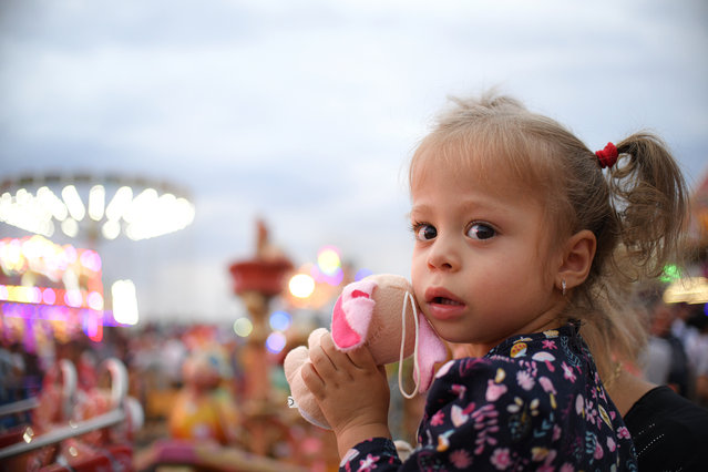 In this picture taken Saturday, September 14, 2019, a little girl holds a toy at an autumn fair in Titu, southern Romania. Romania's autumn fairs are a loud and colorful reminder that summer has come to an end and, for many families in poorer areas of the country, one of the few affordable public entertainment events of the year. (Photo by Andreea Alexandru/AP Photo)