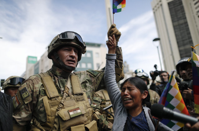 A woman cries in front of soldiers guarding a street during a march of supporters of former President Evo Morales in downtown La Paz, Bolivia, Friday, November 15, 2019. Morales resigned on Nov. 10 at military prompting following massive nationwide protests over suspected vote-rigging in an election in which he claimed to have won a fourth term in office. An Organization of American States audit of the vote found widespread irregularities. (Photo by Natacha Pisarenko/AP Photo)
