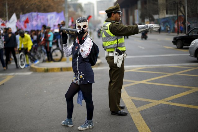 A demonstrator wearing a mock school uniform costume is pictured next to a traffic police officer during a rally held to support women's rights to an abortion in Santiago, Chile, July 25, 2015. (Photo by Ivan Alvarado/Reuters)