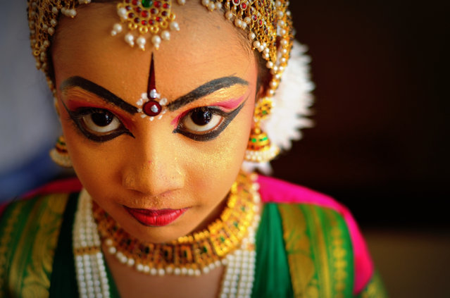 """""""Prodigy in the making..."""" This shot was taken just after her """"arangetram"""" – her first ever public show, at the Guruvayur temple, India. Wanted to capture the colourful makeup, ornaments, silk saree and the kid's expression. Photo location: Guruvayur, Kerala, India. (Photo and caption by Jessu Paul/National Geographic Photo Contest)"""