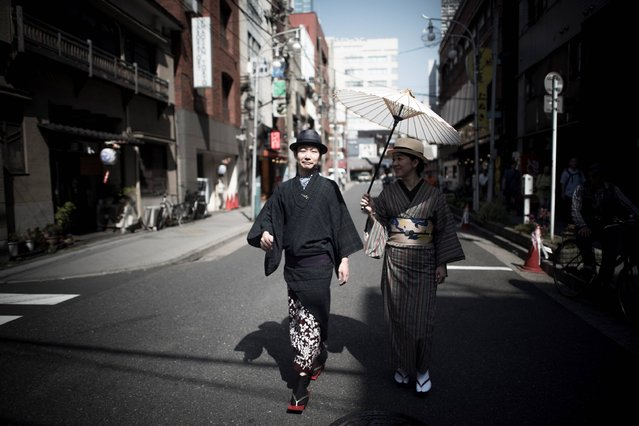 In this picture taken on May 21, 2017, a couple dressed in traditional Japanese costume walk along a street during the Sanja Matsuri festival in Tokyo. (Photo by Fred Dufour/AFP Photo)