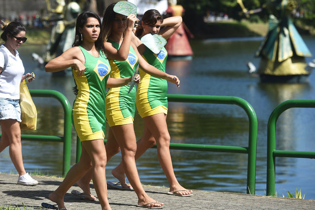 Woman wearing Brazil dresses are seen prior to the Group G football match between Germany and Portugal at the Fonte Nova Arena in Salvador during the 2014 FIFA World Cup on June 16, 2014. (Photo by Dimitar Dilkoff/AFP Photo)