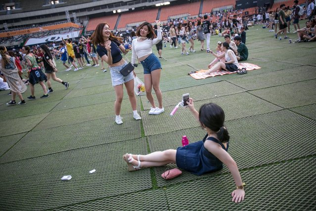 South Korean youths take snapshots while they dance to electronic music during the Ultra Music Festival Korea at Olympic Stadium on June 10, 2016 in Seoul, South Korea. (Photo by Jean Chung/Getty Images)