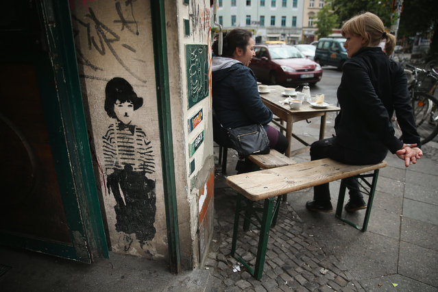 A small figure of Charlie Chaplin peeks out from the entrance to a cafe in Oranienstrasse in Kreuzberg district on June 26, 2014 in Berlin, Germany. Berlin, with its long tradition of counter-culture, has become a mecca for street art of all dimensions and messages. (Photo by Sean Gallup/Getty Images)