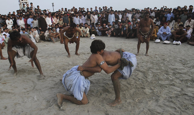 "People watch a traditional style of wrestling called ""Malakhra"" during their visit to Clinfton beach to celebrate Eid al-Fitr holidays in Karachi, Pakistan, Sunday, July 19, 2015. The three-day holidays of Eid al-Fitr marks the end of the holy fasting month of Ramadan. (Photo by Farid Khan/AP Photo)"