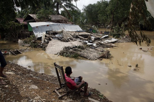 A local resident sitting on a chair looks at his damaged residence by flood in Myauk U, Rakhine State, western Myanmar, Tuesday, August 4, 2015. (Photo by Khin Maung Win/AP Photo)